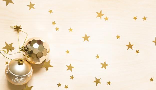 Dekorację świąteczną złote kule i gwiazdy na drewnianym tle.