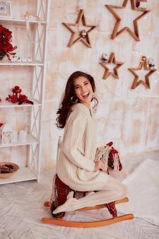 Dekoracje świąteczne. ciepłe kolory. powabna brunetki kobieta w beżowym pulowerze