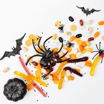 Dekoracje świąteczne halloween, kolorowe cukierki, nietoperze, pająki na białym tle. płaski układanie, widok z góry