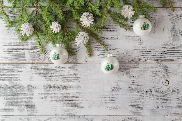 Dekoracje świąteczne i noworoczne na białej powierzchni drewna. piękne choinki zbliżenie dekorować piłki. miejsce na twój tekst