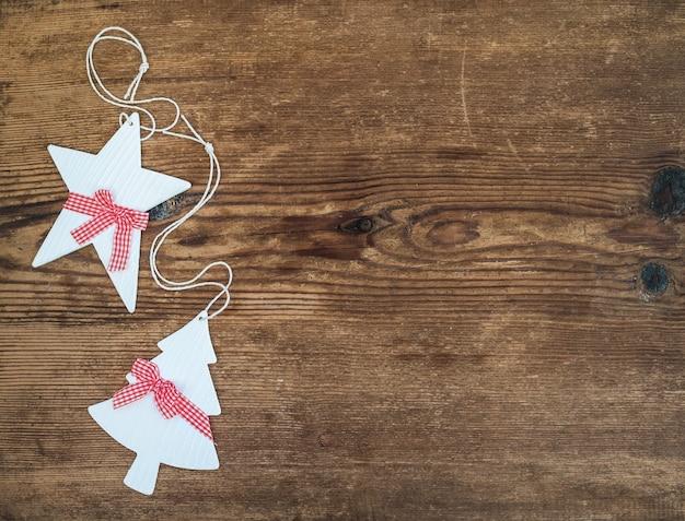 Dekoracje świąteczne lub noworoczne. biel malował gwiazdowego i futerkowego drzewa nad drewnianym tłem, odgórny widok