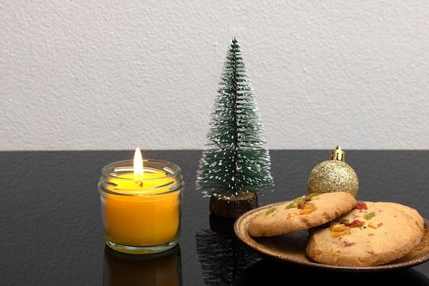 Dekoracje świątecznego stołu ze świecą zapachową i talerzem herbatników ze skórką pomarańczy
