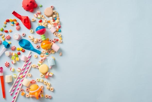 Dekoracje urodzinowe dla dziewczynki. niebieski stół z góry z babeczkami, napojami i gadżetami imprezowymi.