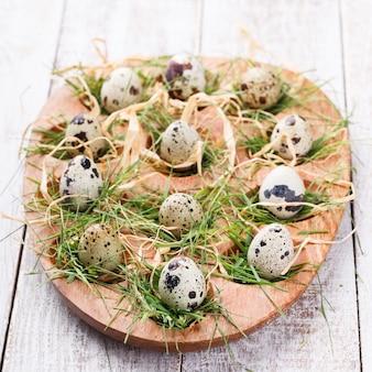 Dekoracje wielkanocne. jaja przepiórcze w gnieździe i trawa na drewnianym stojaku.