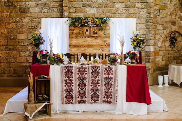 Dekoracje wykonane z drewna i polnych kwiatów serwowane na odświętnym stole w stylu rustykalnym do ceremonii ślubnej.