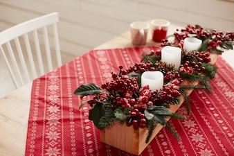 Dekoracje zimowe. Przygotowania do studia. Drewniany naczynie z czerwonymi jagodami i kwiatami
