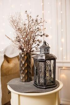 Dekoracyjna antyczna srebrna lampa retro na białym stoliku w salonie. wystrój wnętrz w domu.