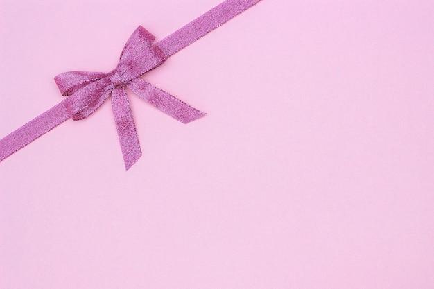 Dekoracyjna błyszcząca faborek z łękiem na różowym tle.