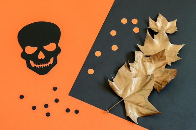 Dekoracyjna czarna czaszka, groszek i złote liście klonu na tle halloween