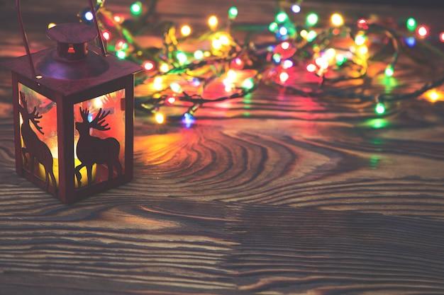 Dekoracyjna czerwona metalowa latarnia z wycięciem z jelenia oświetlona świecącą świecą z lampką bożonarodzeniową i copyspace na nowy rok lub boże narodzenie
