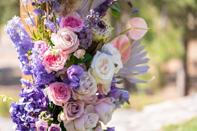 Dekoracyjna dekoracja łuku ślubnego ze świeżymi kwiatami. organizowanie ceremonii ślubnej na świeżym powietrzu. szczegóły dekoracji