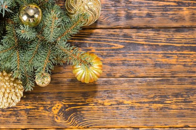 Dekoracyjna dekoracja narożna bożonarodzeniowa w kolorze złotym z ozdobnymi bombkami na zielonej gałęzi sosny na tle drewna rustykalnego tekstury z copyspace
