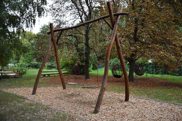 Dekoracyjna drewniana huśtawka na dwa siedzenia na tle letniego parku