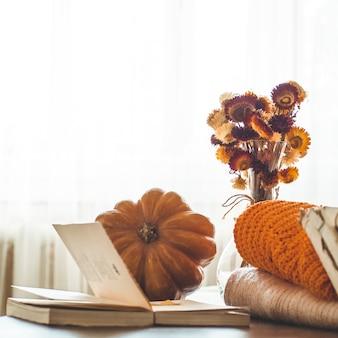 Dekoracyjna dynia, suszone kwiaty, książki, ciepłe swetry. czytanie w jesienny dzień. jesienne książki. jesienne czytanie. przytulny nastrój.