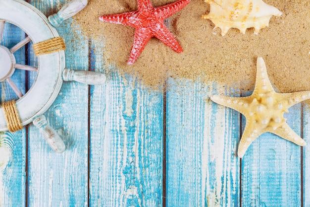 Dekoracyjna kierownica z rozgwiazdą, muszelkami na piaszczystej plaży i drewnianymi deskami
