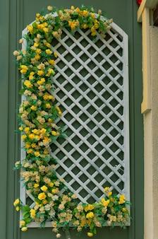 Dekoracyjna krata drewniana ze sztucznymi kwiatami jako dekoracja elewacji budynku od strony ulicy.