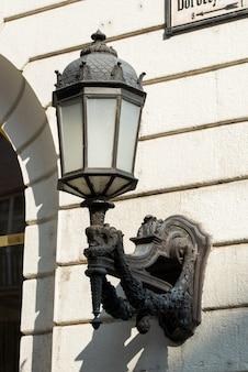 Dekoracyjna lampa uliczna montowana na elewacji budynku