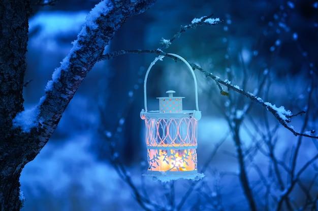 Dekoracyjna latarnia bożonarodzeniowa z płonącą świecą wiszącą na gałęzi pokrytej śniegiem jodły w winter park. nowy rok świąteczna karta, plakat, projekt pocztówki.