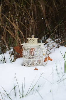 Dekoracyjna latarnia z płonącą świecą w winter park na śniegu wieczorem.