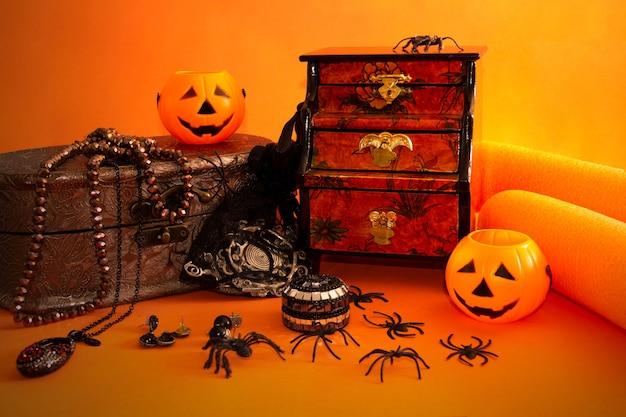 Dekoracyjna martwa natura halloween z pudełkiem na biżuterię, dyniami, pająkami i zabytkowymi przedmiotami