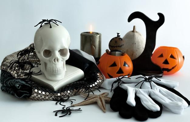 Dekoracyjna martwa natura na halloween z dyniami, czaszkami, pająkami i świecami