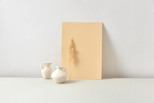 Dekoracyjna nowoczesna kompozycja z rzemieślniczych białych ceramicznych wazonów z suchymi naturalnymi gałązkami kwiatów i pionowo stojącym tekstem zgnilizny papierowej karty na jasnoszarym tle, kopia przestrzeń. koncepcja naturalnego eko.