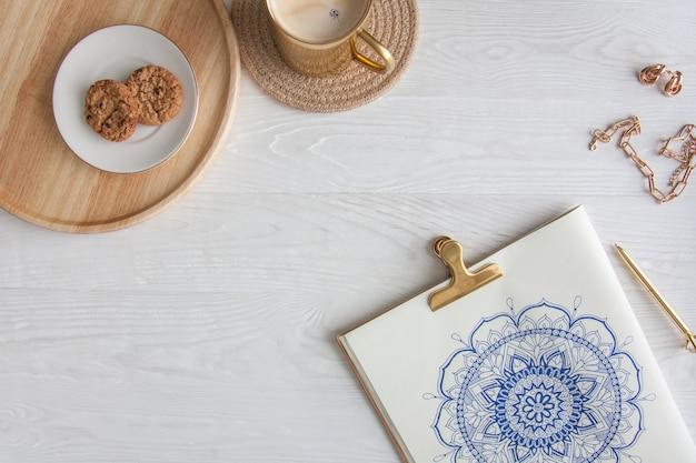 Dekoracyjna okrągła mandala kwiatowa narysowana na białym prześcieradle. domowy relaks, hobby i odpoczynek. kawa i ciasteczka na białym tle.