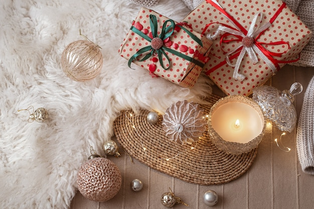 Dekoracyjna płonąca świeca na tle prezentów świątecznych z przytulnymi rzeczami i detalami wystroju z bliska.