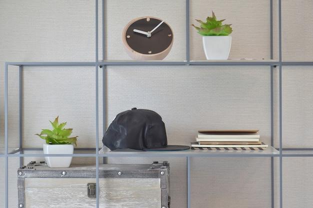 Dekoracyjna półka na ścianie z książkami, czarnymi czapkami, drewnianym zegarem i wazą