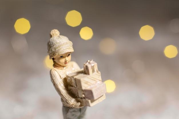 Dekoracyjna świąteczna figurka dziewczyny trzymającej w rękach pudełka z prezentami na boże narodzenie.