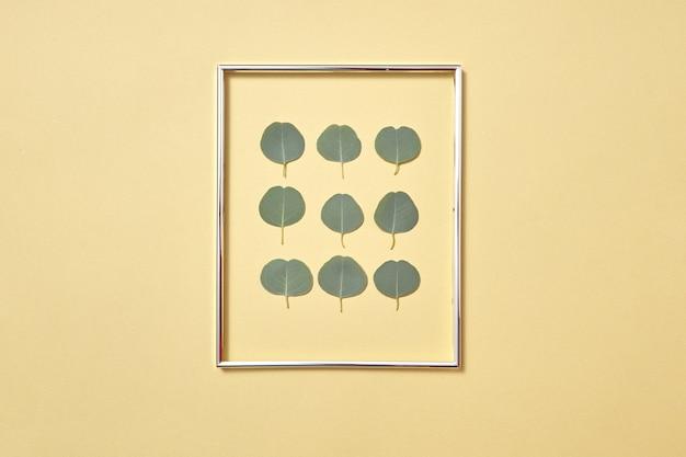 Dekoracyjna świąteczna kartka z ramą z wiecznie zielonych świeżych naturalnych liści eukaliptusa na piaskowej żółtej ścianie, miejsce na kopię.