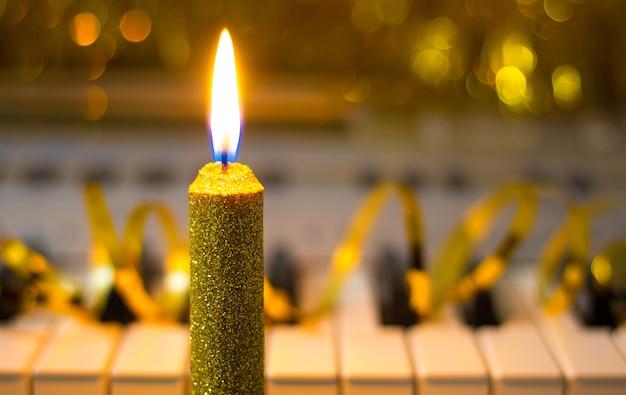 Dekoracyjna świeca na tle fortepianu w złotych odcieniach_