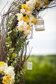 Dekoracyjne białe klatki dla ptaków wiszą na ołtarzu weselnego wesela