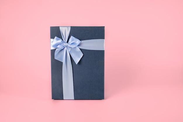 Dekoracyjne ciemnoniebieskie pudełko z jasnoniebieską kokardą na różowym pastelowym tle, zapakowane pudełko z wycinek ścieżki