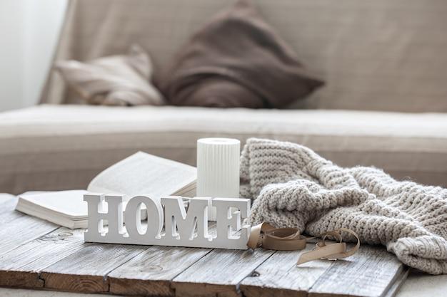 Dekoracyjne drewniane słowo do domu, książki, świeca i element z dzianiny na niewyraźne tło.