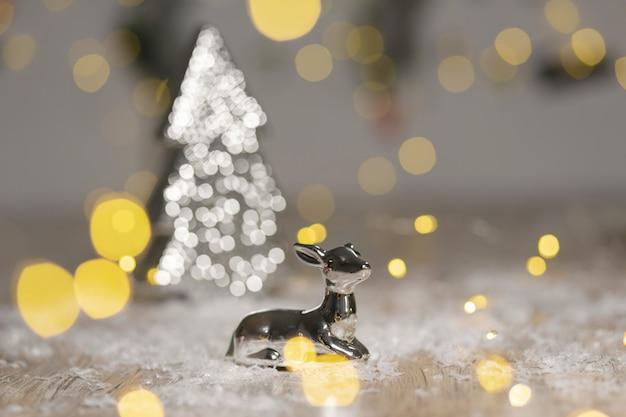 Dekoracyjne figurki o tematyce bożonarodzeniowej, statuetka leżącego jelenia przy choince,,