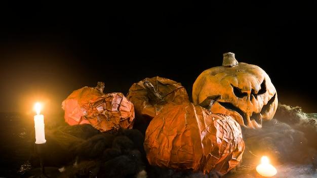 Dekoracyjne halloweenowe banie kłama wśród płonących świeczek