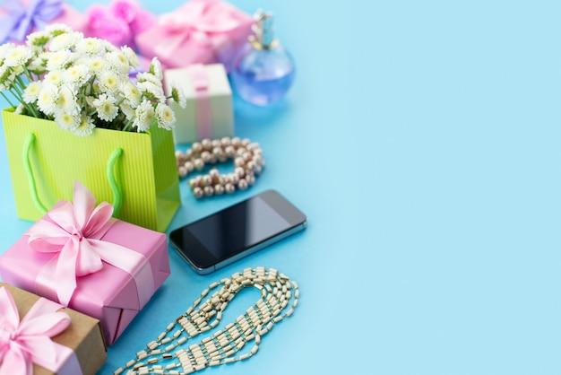 Dekoracyjne kompozycje pudełka z prezentami kwiaty biżuteria damska zakupy wakacje niebieskie tło.