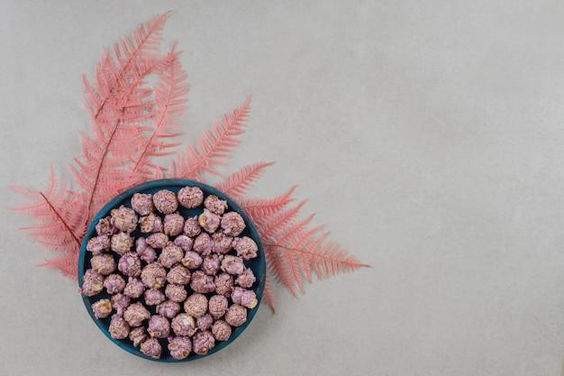 Dekoracyjne liście pod miską popcornu cukierków na marmurowym tle.