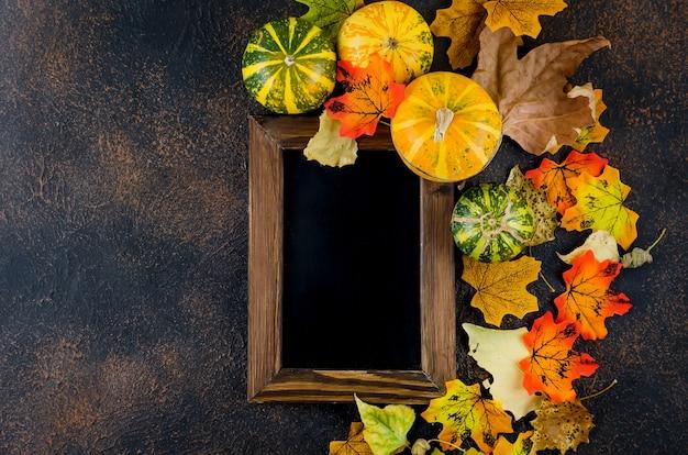 Dekoracyjne mini dynie z jesiennych suszonych liści na ciemnym tle betonu, koncepcja jesień, miejsce na kopię, koncepcja jesienna lub jesienne wakacje, święto dziękczynienia, miejsce