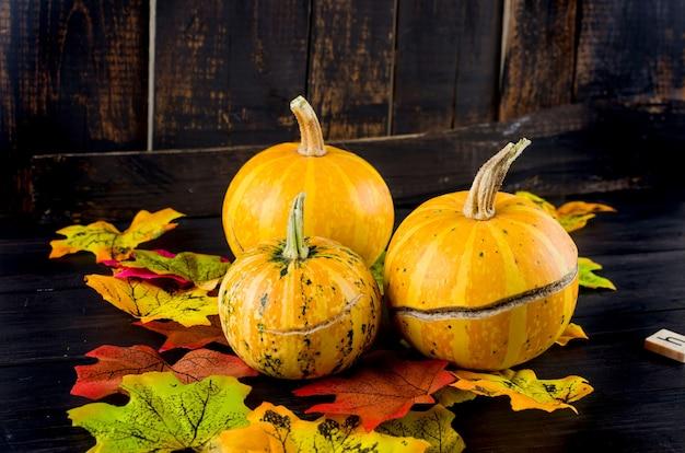 Dekoracyjne mini dynie z suszonych liści jesienią na ciemnym starym drewnianym tle, koncepcja jesień lub jesienne wakacje, święto dziękczynienia, miejsce