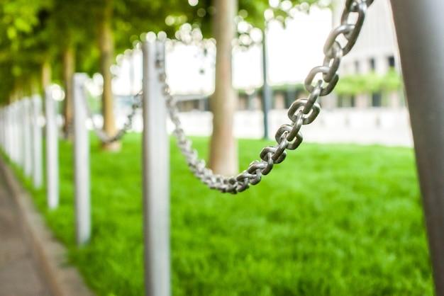 Dekoracyjne ogrodzenie posesji prywatnej w postaci stalowego łańcucha. trawnik, trawa, drzewa. poziome zdjęcie