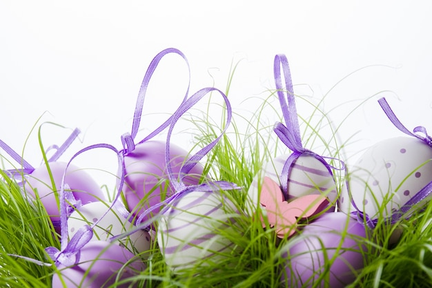 Dekoracyjne pisanki z purpurową wstążką na trawie