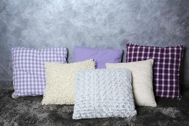 Dekoracyjne poduszki na szarej ścianie
