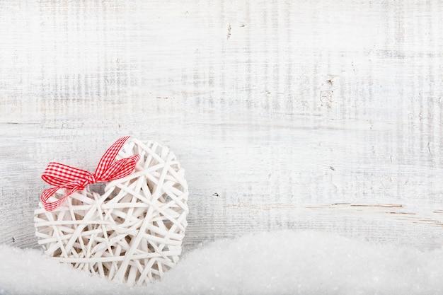 Dekoracyjne serce w śniegu na drewnianym tle