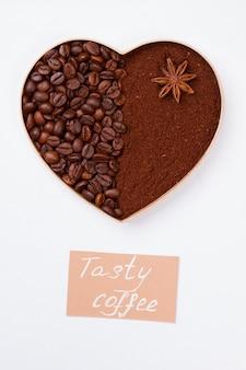 Dekoracyjne serce z ziaren kawy i proszku z anyżem. na białym tle na białej powierzchni
