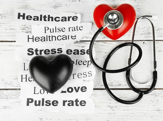 Dekoracyjne serce ze stetoskopem na papierowych notatkach, na drewnianym