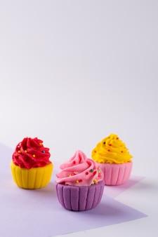 Dekoracyjne wielobarwne cukrowe babeczki na jasnym tle z kropią