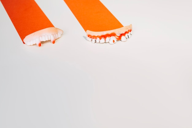 Dekoracyjne zdeformowane zęby człowieka na pomarańczowym papierze