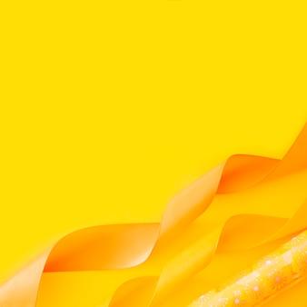 Dekoracyjne zwinięte plamy wstążki i papier prezent na żółtym tle